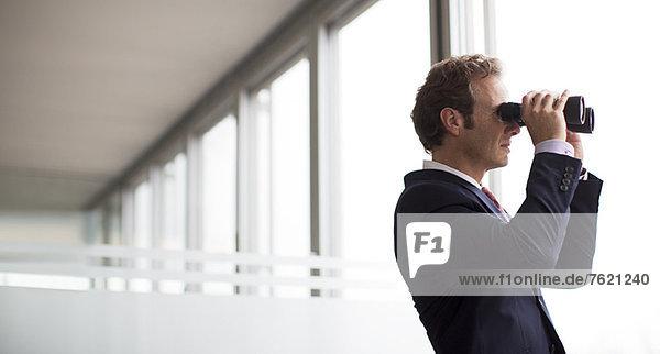 Geschäftsmann mit Fernglas am Bürofenster
