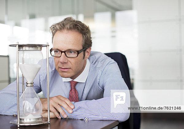 Geschäftsmann beobachtet Sanduhr am Schreibtisch