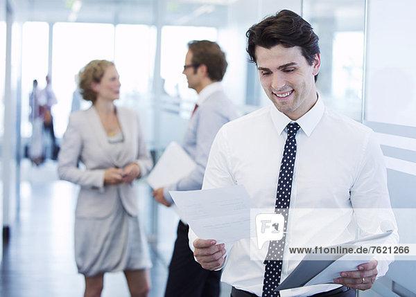 Geschäftsmann beim Lesen von Papieren im Büroflur