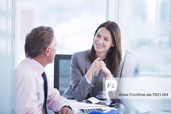 Geschäftsleute sprechen am Schreibtisch