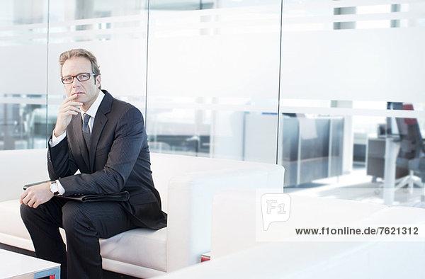 Geschäftsmann sitzt auf dem Sofa in der Bürolobby