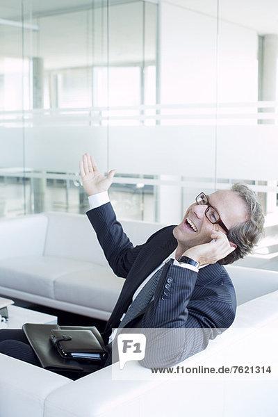 Geschäftsmann beim Telefonieren auf dem Sofa