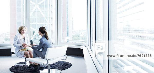 Geschäftsfrauen im Gespräch in der Bürolobby