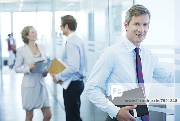 Geschäftsmann lächelt im Büroflur