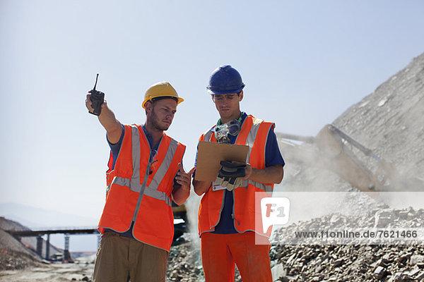 Arbeiter reden im Steinbruch