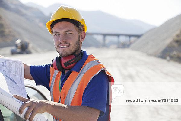 Arbeiter beim Lesen von Bauplänen im Steinbruch