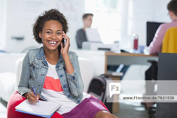 Frau macht sich Notizen auf dem Handy im Büro