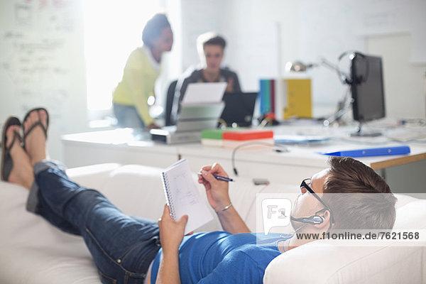 Geschäftsmann beim Notieren auf dem Sofa im Büro