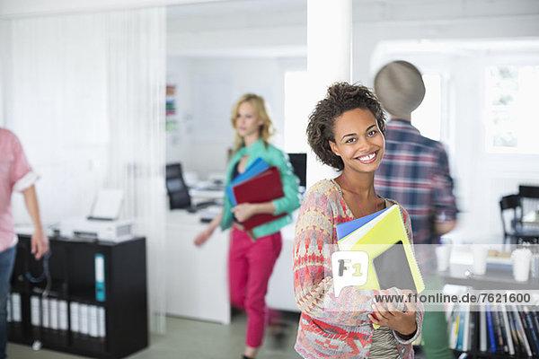 Geschäftsfrau mit Mappen im Büro