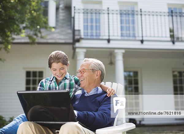 Mann mit Laptop und Enkelin im Freien Mann mit Laptop und Enkelin im Freien