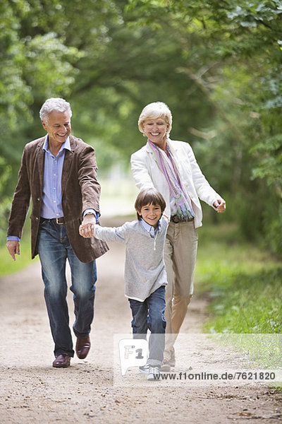 Couple walking with grandson on rural road