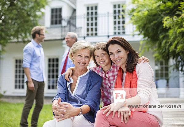 Familie lächelt gemeinsam vor dem Haus