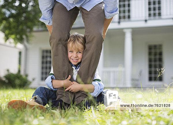 Junge  der aus den Beinen seines Vaters herausguckt. Junge, der aus den Beinen seines Vaters herausguckt.