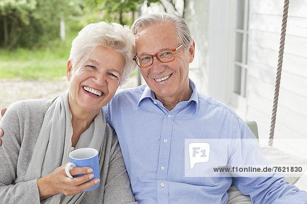 Lächelndes Paar sitzt auf der Veranda-Schaukel Lächelndes Paar sitzt auf der Veranda-Schaukel