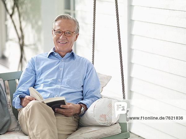 Mann liest Buch auf Veranda-Schaukel Mann liest Buch auf Veranda-Schaukel
