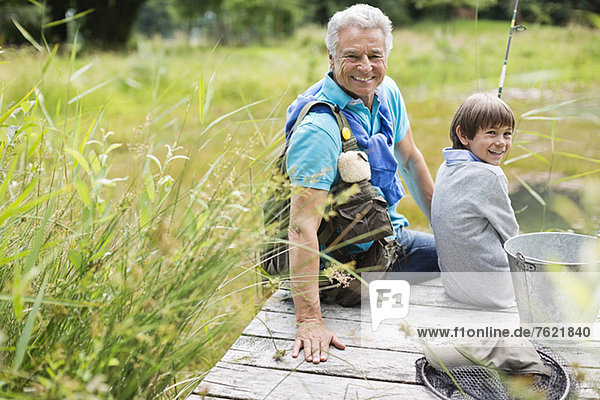 Mann beim Angeln mit Enkel auf Holzdock Mann beim Angeln mit Enkel auf Holzdock