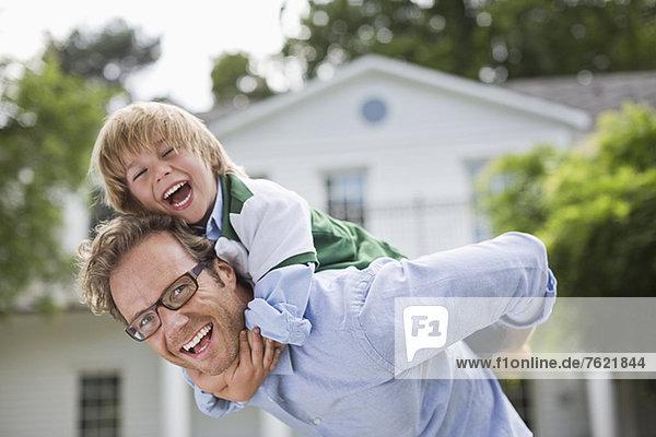 Mann  der seinen Sohn huckepack im Freien trägt. Mann, der seinen Sohn huckepack im Freien trägt.