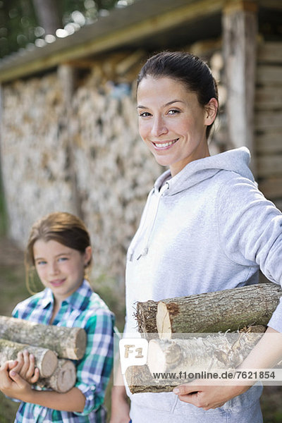 Mutter und Tochter mit Brennholz im Freien Mutter und Tochter mit Brennholz im Freien