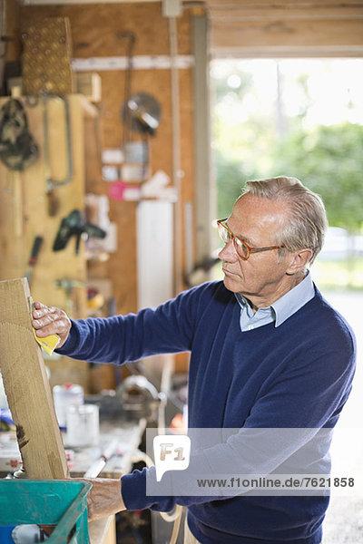 Mann arbeitet in der Garage Mann arbeitet in der Garage