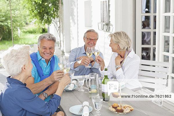 Freunde stoßen sich mit Wein im Freien an. Freunde stoßen sich mit Wein im Freien an.