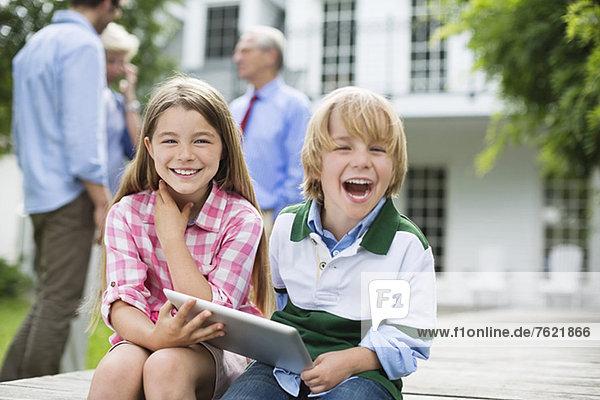Kinder  die das digitale Tablett gemeinsam im Freien benutzen Kinder, die das digitale Tablett gemeinsam im Freien benutzen