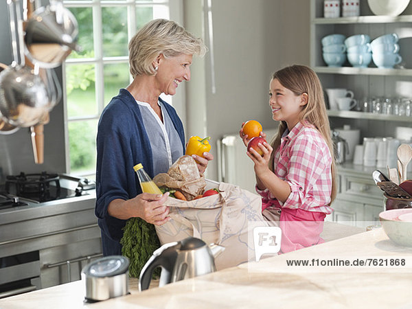 Frau und Enkelin beim Entladen von Lebensmitteln Frau und Enkelin beim Entladen von Lebensmitteln