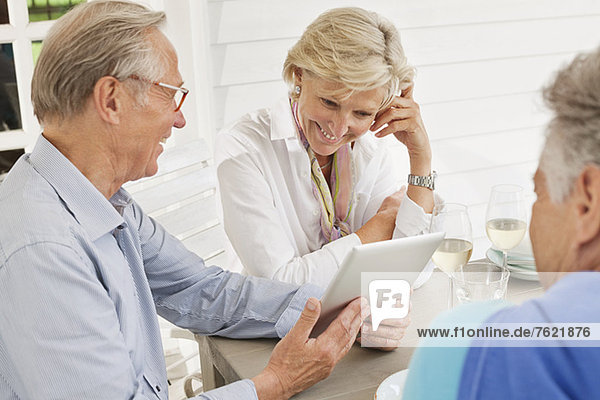 Paar mit digitalem Tablett am Tisch im Freien Paar mit digitalem Tablett am Tisch im Freien