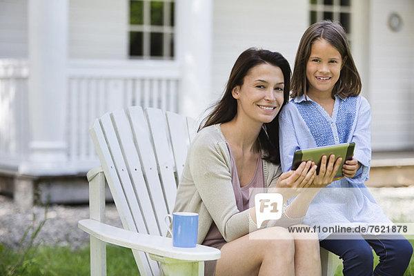 Mutter und Tochter mit digitalem Tablett im Freien Mutter und Tochter mit digitalem Tablett im Freien