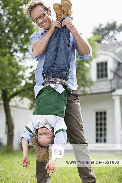 Vater und Sohn spielen zusammen im Freien Vater und Sohn spielen zusammen im Freien