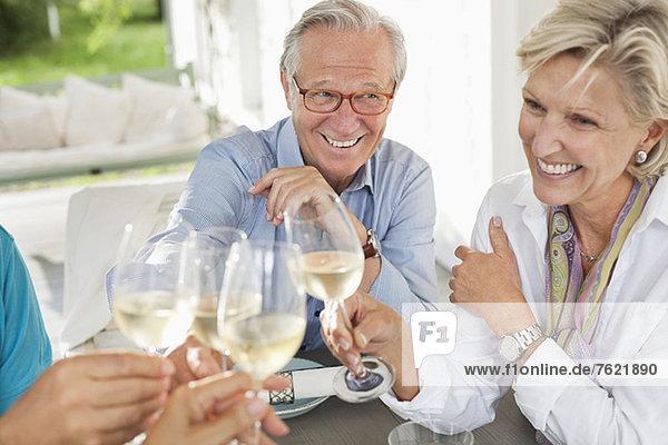 Freunde stoßen sich gegenseitig mit Wein an. Freunde stoßen sich gegenseitig mit Wein an.
