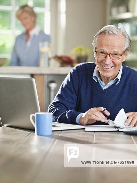 Mann mit Laptop am Küchentisch