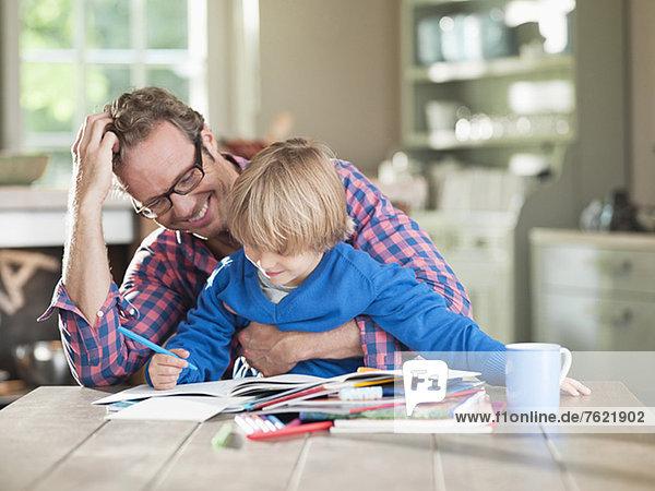 Vater und Sohn machen Hausaufgaben am Küchentisch Vater und Sohn machen Hausaufgaben am Küchentisch