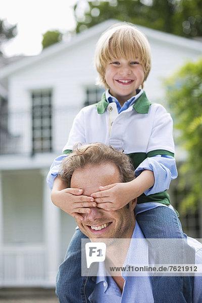 Junge  der Vaters Augen im Freien bedeckt. Junge, der Vaters Augen im Freien bedeckt.