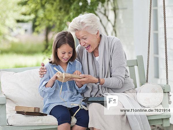 Frau schenkt Enkelin in der Veranda-Schaukel Frau schenkt Enkelin in der Veranda-Schaukel