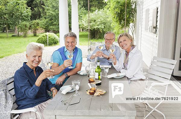 Freunde stoßen sich bei Tisch mit Wein an.