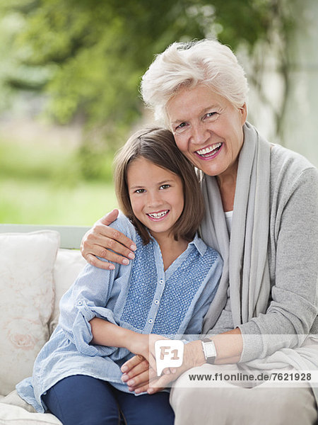 Frau und Enkelin lächelnd auf der Veranda-Schaukel Frau und Enkelin lächelnd auf der Veranda-Schaukel