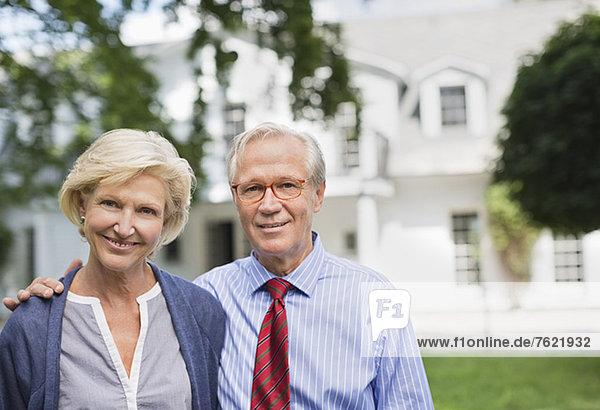Paar lächelt zusammen vor dem Haus