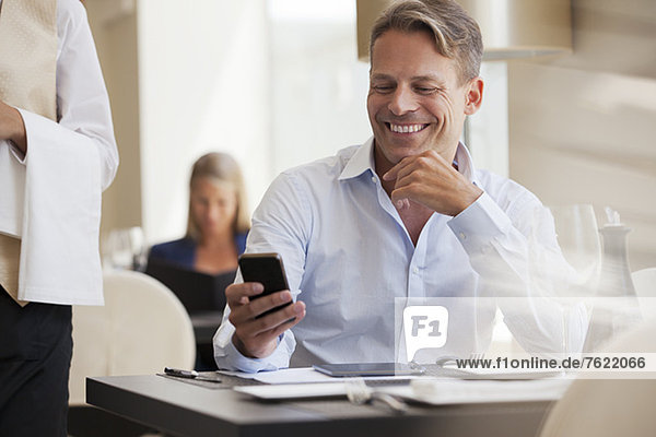 Geschäftsmann mit Handy im Restaurant