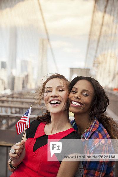 Lächelnde Frauen winken mit amerikanischer Flagge