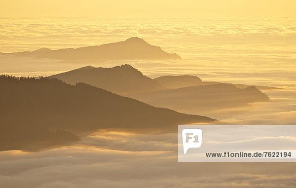 Luftaufnahme der Berggipfel über Wolken bei Sonnenuntergang