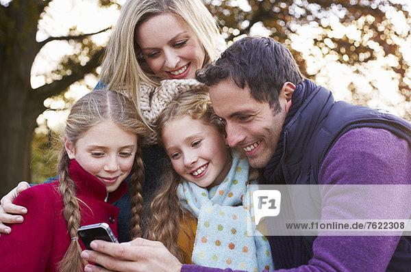 Familie mit Handy im Freien