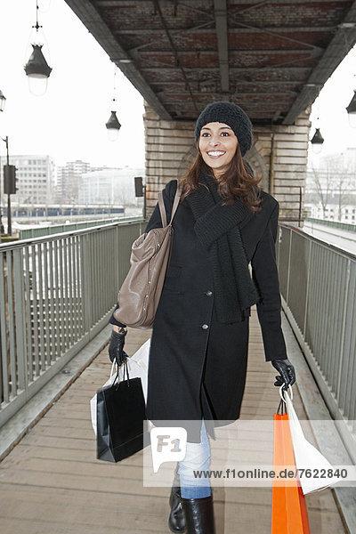 Frau mit Einkaufstaschen auf dem Bahnsteig