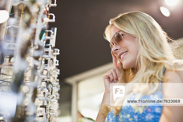 Frau probiert Sonnenbrille im Laden an Frau probiert Sonnenbrille im Laden an