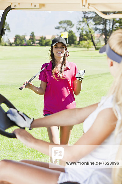 Women playing golf on course