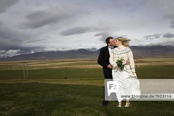 Neuvermähltes Ehepaar beim Küssen im ländlichen Raum