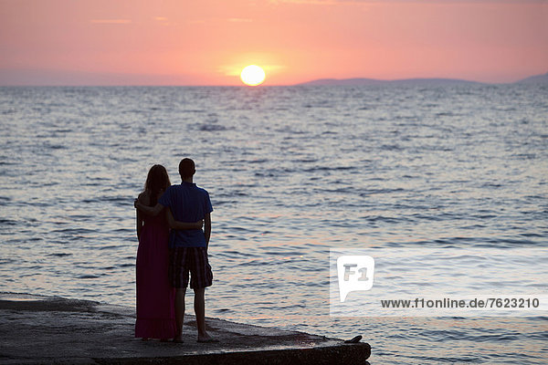 Paar beobachtet Sonnenuntergang am Pier