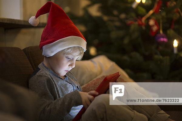 Junge mit Nikolausmütze mit Tablet-Computer