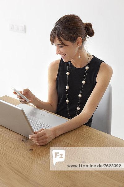 Geschäftsfrau mit Handy am Schreibtisch