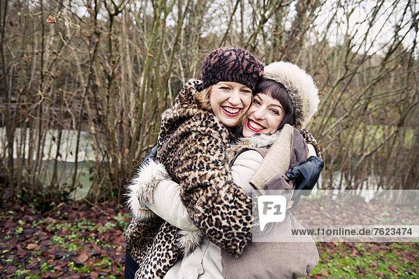 Lächelnde Frauen  die sich im Wald umarmen