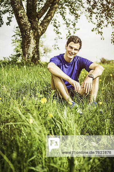 Lächelnder Mann im hohen Gras sitzend
